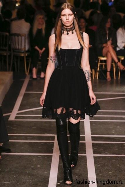 Черное новогоднее платье длиной выше колен, с корсетным верхом и гипюровой юбкой в сочетании с сапогами-чулками черного тона с открытым носком от Givenchy.