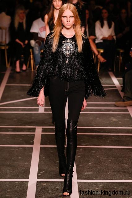 Вечерние зауженные брюки черного цвета в тандеме с меховым жилетом черного тона и высокими кожаными сапогами с открытым носом от Givenchy.