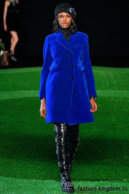 Высокие женские сапоги черного цвета без каблуке, с пряжками и заклепками в сочетании с пальто ярко-синего цвета от Marc by Marc Jacobs.
