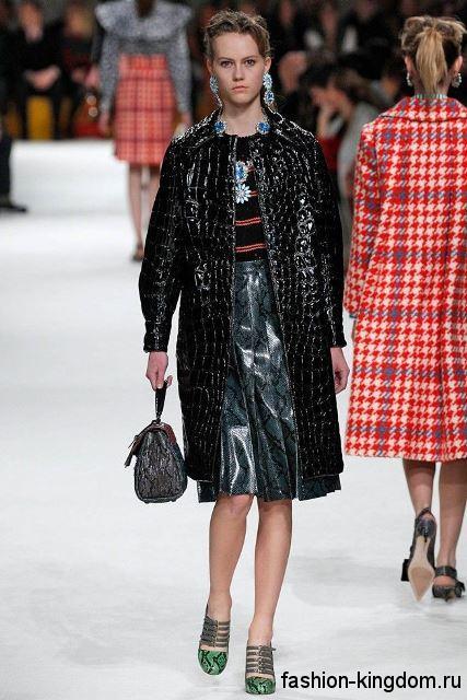 Кожаный черный плащ с фактурным принтом, длиной до колен дополняется серой юбкой-миди со змеиным рисунком и украшениями модного сезона осень-зима 2015-2016 от Miu Miu.