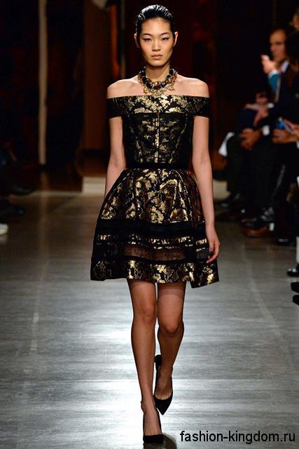 Короткое платье черно-золотистой расцветки с пышной юбкой гармонирует с украшениями в тон наряду модного сезона осень-зима 2015-2016 от Oscar de la Renta.