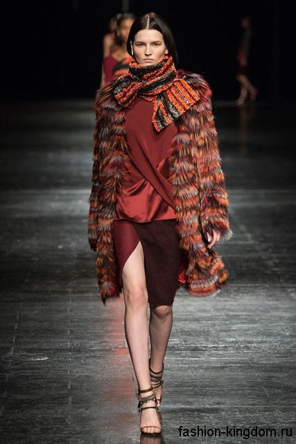 Шуба рыже-красной расцветки дополняется блузкой и юбкой бордового тона, широким шарфом черно-рыжего цвета и коричневыми босоножками на каблуке от Prabal Gurung.