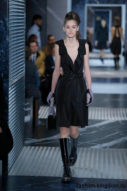 Лакированные высокие сапоги черного цвета без каблука в тандеме с черным платьем без рукавов от Prada.