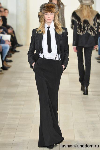 Костюм черного цвета, состоящий из длинной юбки и классического жакета, дополняется черным галстуком и меховой шапкой модного сезона осень-зима 2015-2016 от Ralph Lauren.