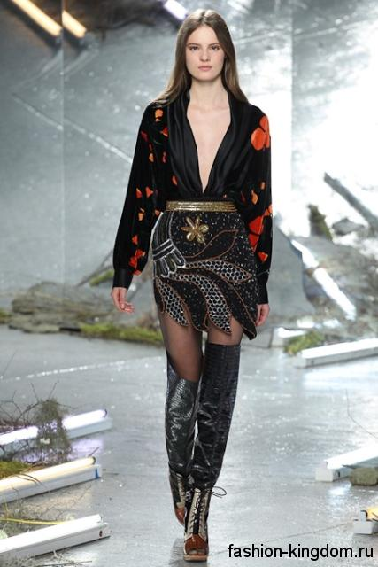 Сапоги-чулки черного цвета на высоком каблуке, со шнуровкой и открытым носком в сочетании с коротким платьем черного тона с красно-золотистыми вставками и глубоким декольте от Rodarte.