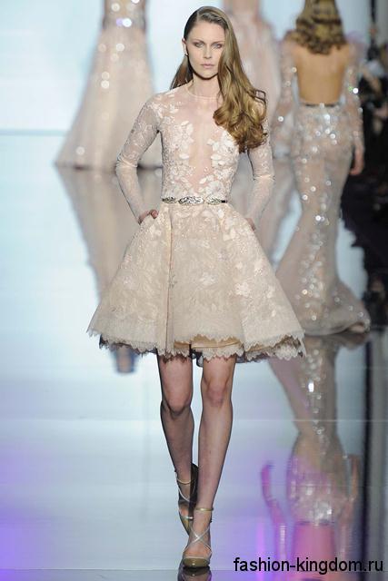 Короткое платье с пышной юбкой для вечернего стиля, выполненное из блестящей ажурной ткани, с длинными рукавами в сочетании с открытыми туфлями на каблуке от Zuhair Murad.