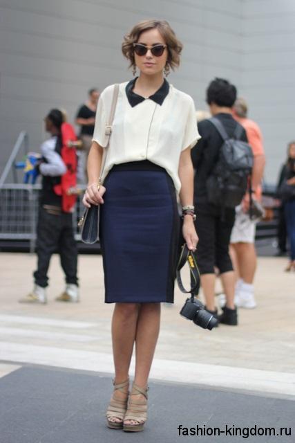 Офисная юбка-карандаш темно-синего цвета, длиной до колен гармонирует с белой блузкой с короткими рукавами.