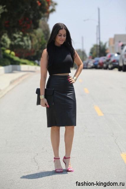 Кожаная юбка-карандаш черного цвета длиной до колен в тандеме с черным топом и розовыми босоножками на шпильке.