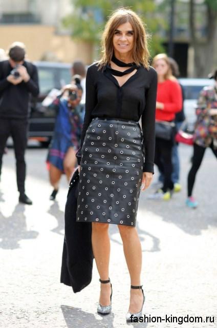 Кожаная юбка-карандаш черного цвета с металлическими вставками в сочетании с шифоновой черной блузкой и серебристыми туфлями.