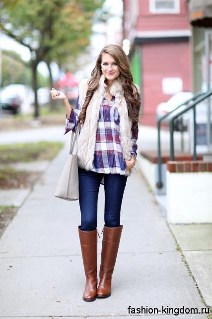 Клетчатая рубашка с длинными рукавами в сочетании с меховой жилеткой, темно-синими джинсами и высокими коричневыми сапогами.