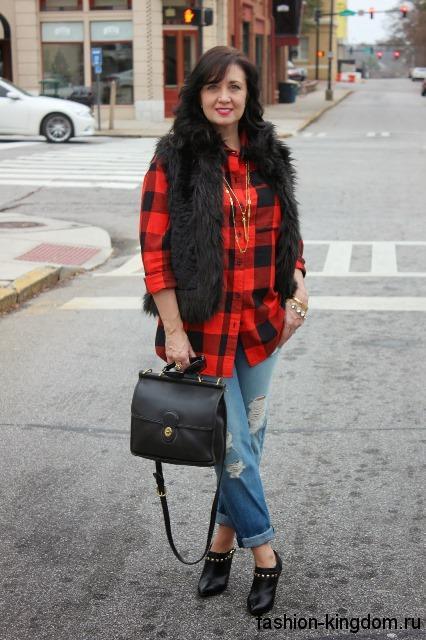 Женская рубашка в клетку красно-черного цвета в сочетании с меховой черной жилеткой и джинсами-бойфрендами светло-синего тона.