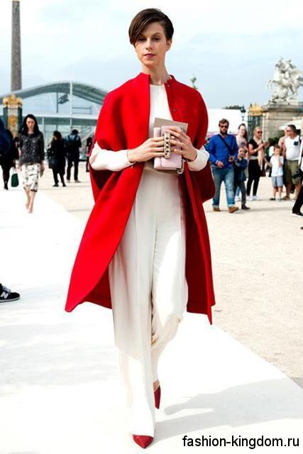 Демисезонное пальто красного цвета длиной до колен, полуприталенного силуэта, с короткими рукавами в сочетании с белым брючным костюмом и красными туфлями.