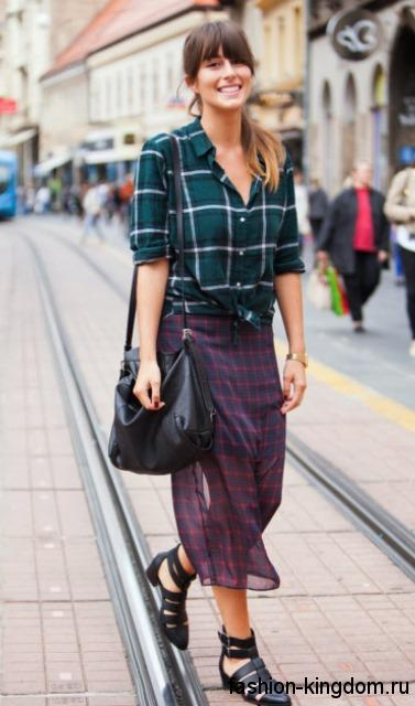 Осенняя рубашка в клетку сине-зеленой расцветки с длинными рукавами в сочетании с черными джинсами и замшевыми черными сапогами на каблуке.