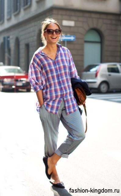 Летняя клетчатая рубашка светлых оттенков, свободного фасона гармонирует с укороченными серыми брюками.