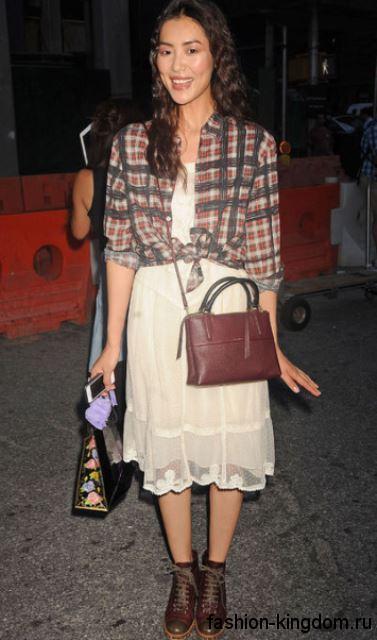 Женская клетчатая рубашка в коричневых тонах дополнит ажурное белое платье длиной до колен.