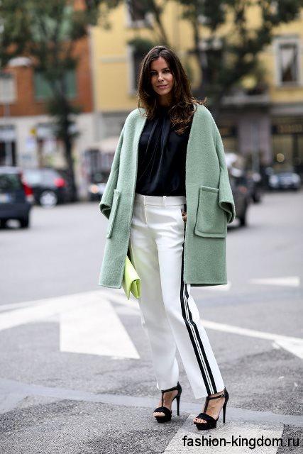 Демисезонное короткое пальто мятного оттенка, с накладными карманами сочетается с черной блузкой и прямыми белыми брюками.