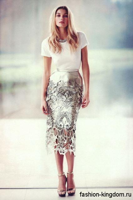 Блестящая вечерняя юбка-карандаш с ажурными вставками сочетается с белой блузкой и золотистыми босоножками на каблуке.