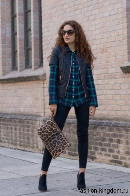 Осенняя клетчатая рубашка сине-бирюзового цвета сочетается с черной жилеткой, укороченными черными брюками и сумочкой леопардовой расцветки.