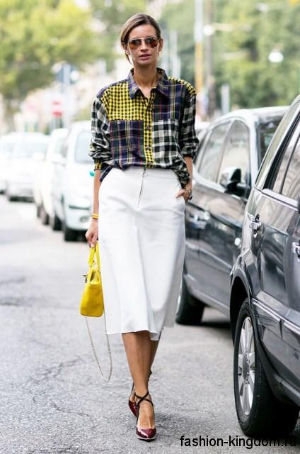 Модная клетчатая рубашка черно-белого цвета с желтыми вставками в тандеме с белой юбкой длиной ниже колен.
