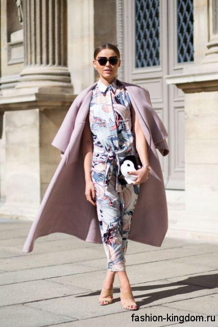 Длинное демисезонное пальто бледно-сиреневого оттенка, с рукавами три четверти сочетается с комбинезоном с абстрактным рисунком.