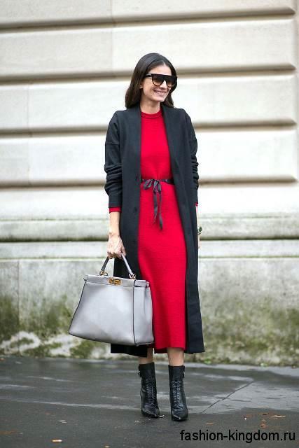 Длинное демисезонное пальто черного цвета в тандеме с длинным платьем красного тона, серебристой сумочкой и черными ботильонами.