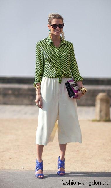 Модная клетчатая рубашка светло-зеленого цвета гармонирует с укороченными белыми брюками и босоножками синего тона.
