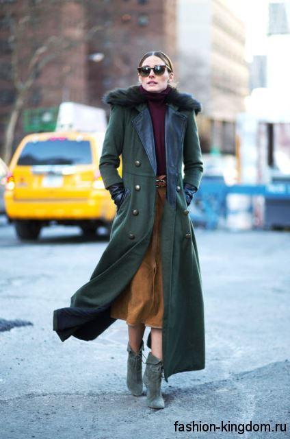 Демисезонное пальто темно-зеленого цвета длиной в пол, с меховым воротником сочетается с ботильонами серого тона на каблуке.