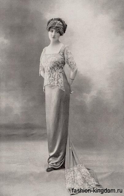 Модное платье 1900-х длиной в пол, с завышенной талией, кружевными рукавами, узкой юбкой и небольшим шлейфом.