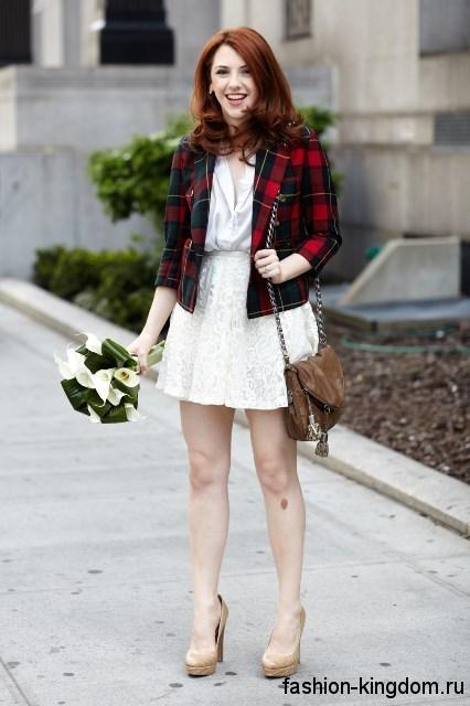 Короткое демисезонное пальто красно-черного цвета в клетку гармонирует с белым платьем-мини и туфлями на высоком каблуке.