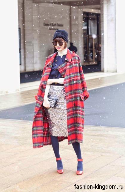 Блестящая юбка-карандаш серебристого цвета, длиной ниже колен сочетается с пальто красного тона в клетку и красными туфлями на каблуке.