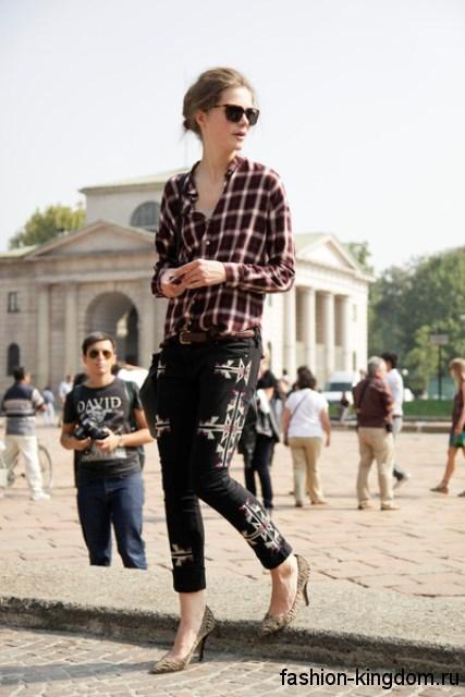 Стильная клетчатая рубашка коричневого тона сочетается с черными брюками с вышивкой и туфлями золотистого цвета на каблуке.