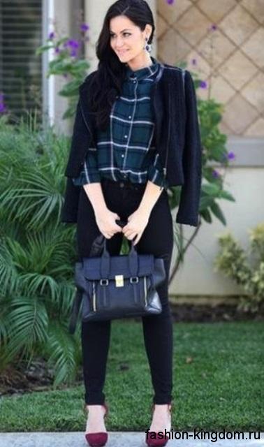 Женская клетчатая рубашка темного тона в сочетании с узкими черными брюками и короткой кожаной курткой для вечернего образа.