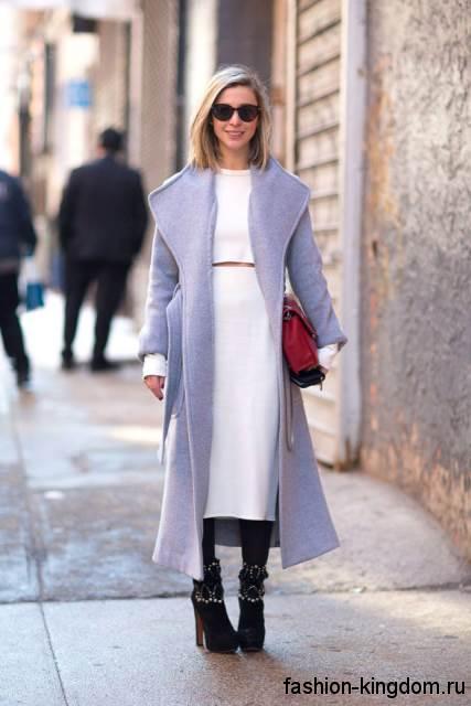 Длинное демисезонное пальто светло-сиреневого цвета в сочетании с белым платьем и ботильонами черного тона на каблуке.