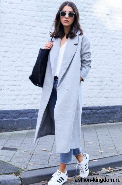 Длинное демисезонное пальто светло-серого цвета, полуприталенного фасона в сочетании с синими джинсами и белыми кроссовками.