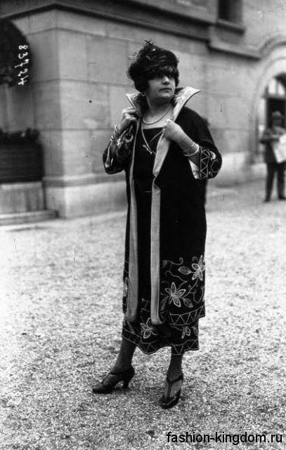 Женское пальто прямого кроя в стиле 1900-х, темного цвета, с рукавами три четверти, украшенное вышивкой.