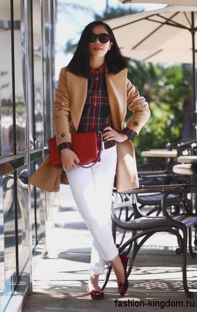 Клетчатая рубашка в темных тонах гармонирует с белыми брюками и демисезонным пальто бежевого оттенка.