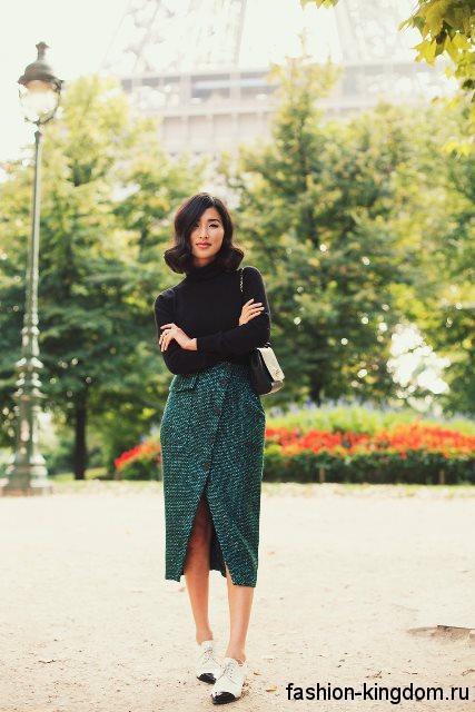 Стильная юбка-карандаш темно-зеленого оттенка, с разрезом, длиной ниже колен в тандеме с черным свитером с воротником стойкой.