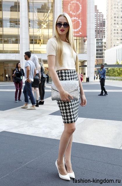 Вечерняя юбка-карандаш черно-белого тона в клетку гармонирует с белым топом с короткими рукавами и белыми туфлями на каблуке.