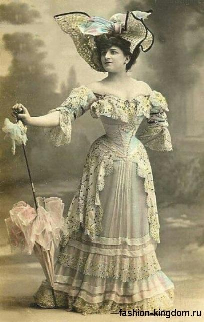 Длинное вечернее платье с S-образным силуэтом, декорированное рюшами, кружевом и бисером.