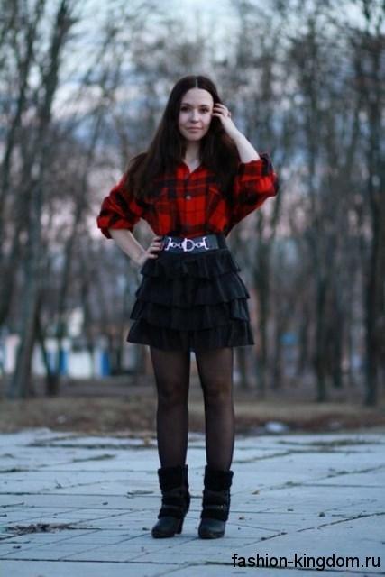 Рубашка в клетку красно-черного цвета с длинными рукавами в тандеме с короткой черной юбкой и сапогами черного тона на каблуке.