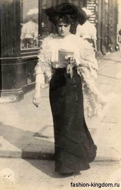 Повседневный образ 1900-х в виде длинной черной юбки узкого силуэта, белой кружевной блузки с черной шляпы.