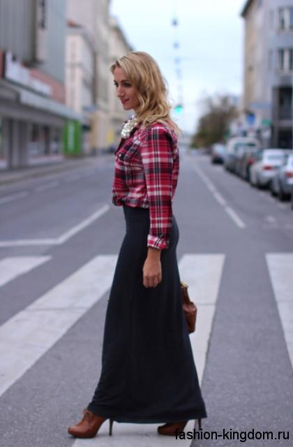 Рубашка в клетку красных оттенков дополняет длинную черную юбку и ботильоны коричневого цвета на высоком каблуке.