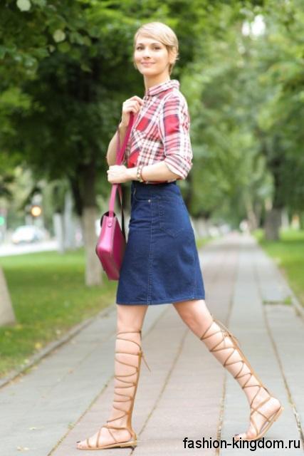 Женская рубашка в клетку красно-белого цвета гармонирует с джинсовой юбкой-миди и босоножками на плоской подошве.