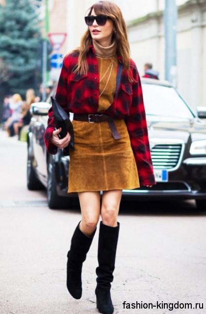 Осенняя клетчатая рубашка красного тона с длинными рукавами сочетается с коротким платьем горчичного оттенка и высокими черными сапогами на каблуке.