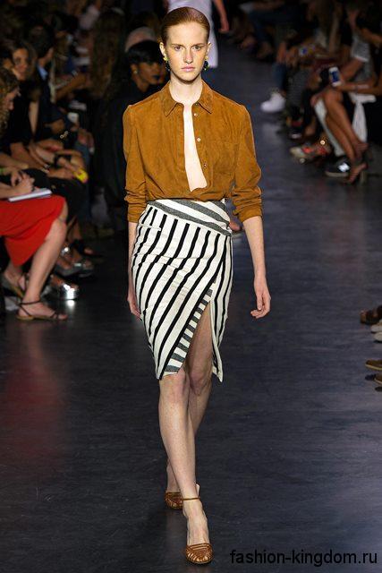 Стильная юбка-карандаш черно-белого цвета в полоску с высоким разрезом из коллекции Altuzarra в сочетании с блузкой горчичного оттенка.