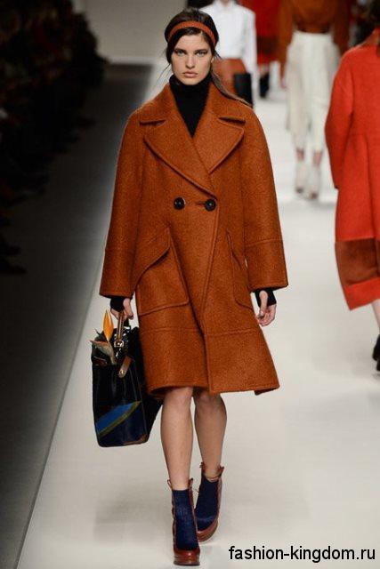 Демисезонное пальто коричневого цвета свободного силуэта, длиной до колен в тандеме с сумочкой и ботильонами черного тона от Fendi.