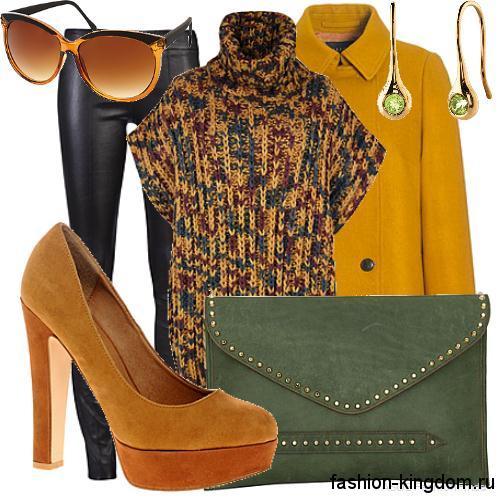 Короткое демисезонное пальто горчичного цвета в тандеме со свитером черно-желтого тона без рукавов и кожаными черными брюками.