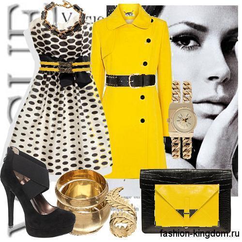 Желтое демисезонное пальто с черными вставками сочетается с платьем черно-белого цвета в стиле ретро и черными туфлями на каблуке.