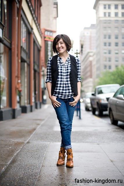 Клетчатая черно-белая рубашка в стиле кэжуал в тандеме с синими джинсами прямого кроя и черной жилеткой.