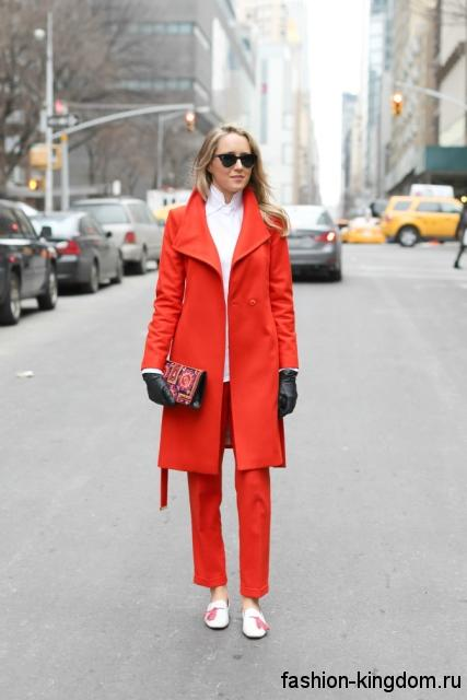 Белые модные туфли без каблука сочетаются с брюками и пальто красного цвета.